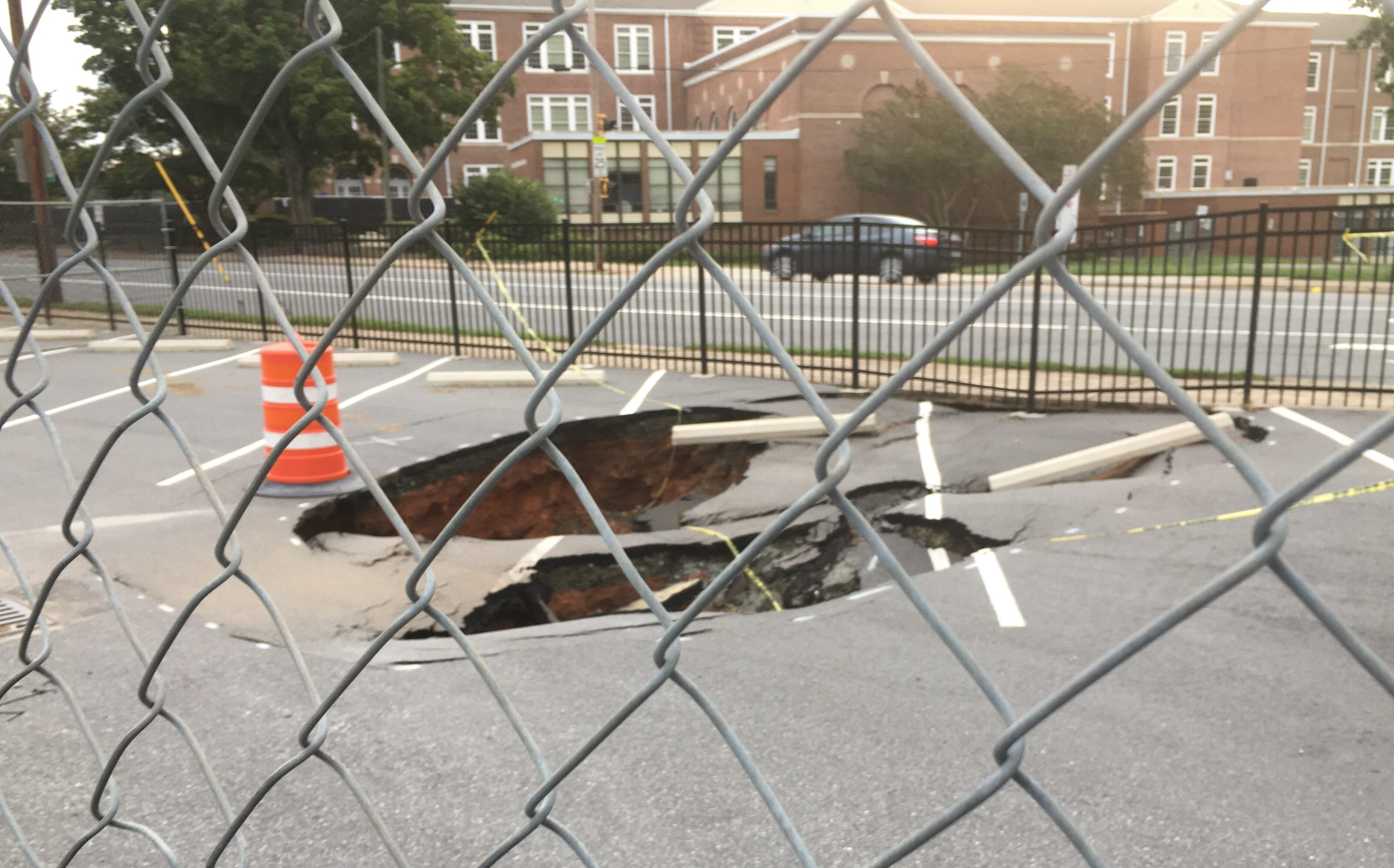 Image shows a sink hole in a parking lot.